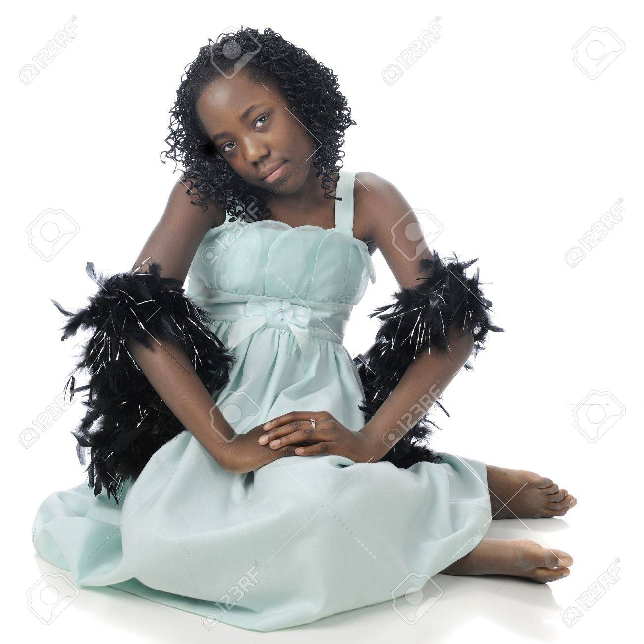 black preteen american preteen: A beautiful tween girl sitting in her soft green dres  with black boas