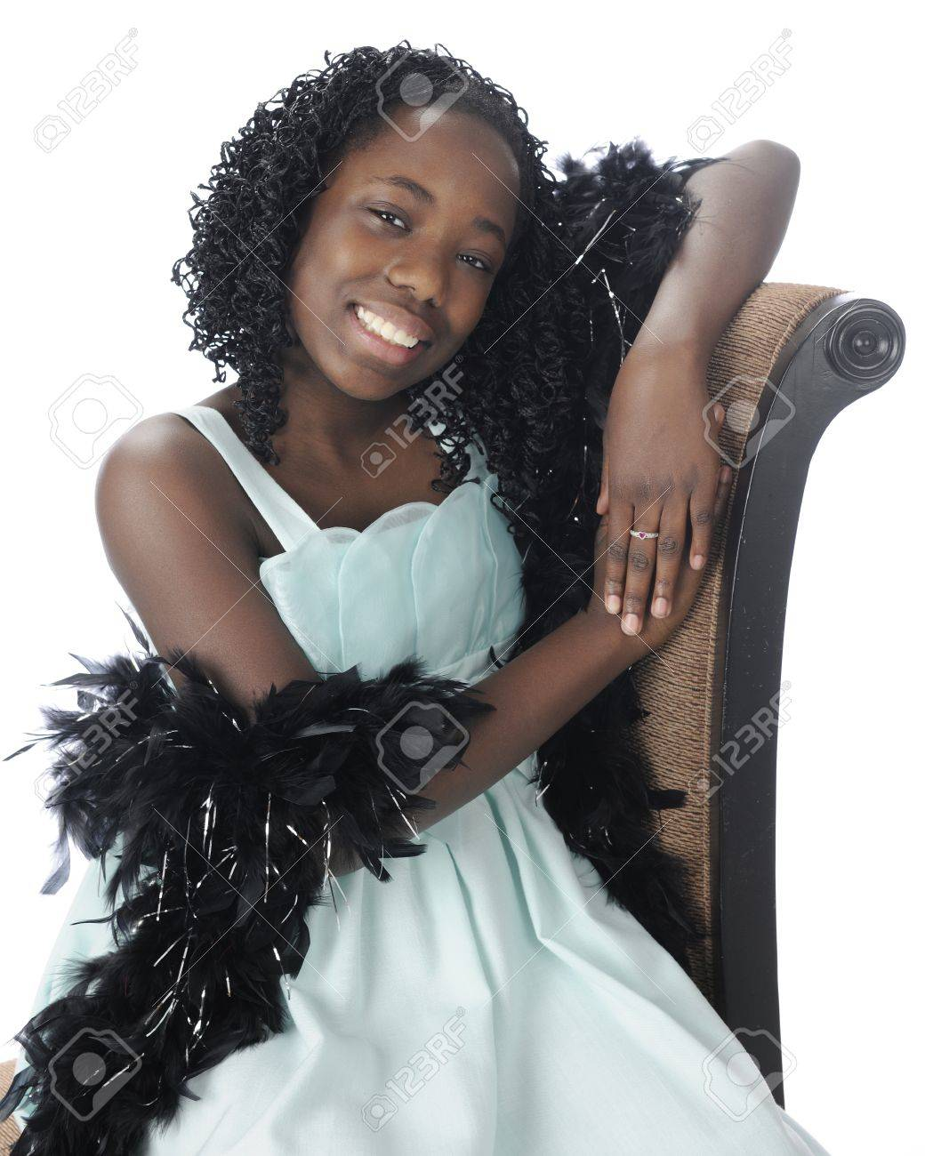 black preteen A happy preteen sitting in her soft green dress with a feathery black boa  draped over
