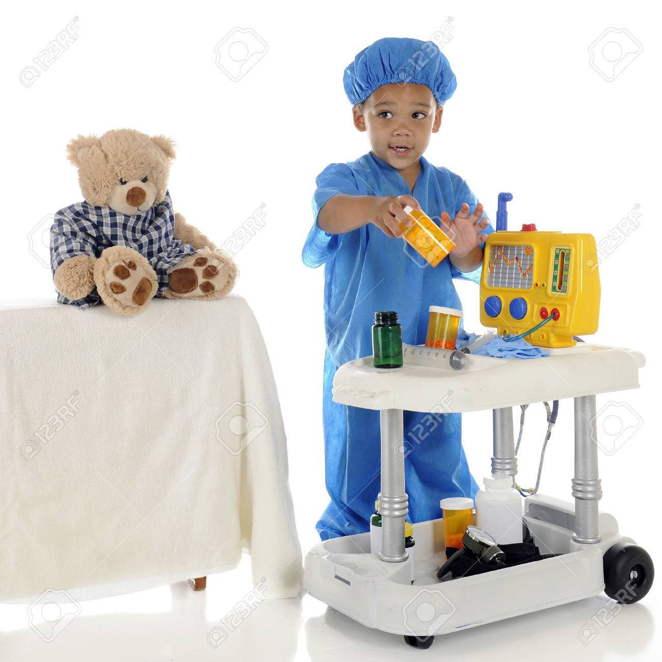 An adorable preschool  doctor  in blue scrubs questioning about the medication he should be giving his patient  toy bear  from his emergency cart   On a white background Stock Photo - 26560455