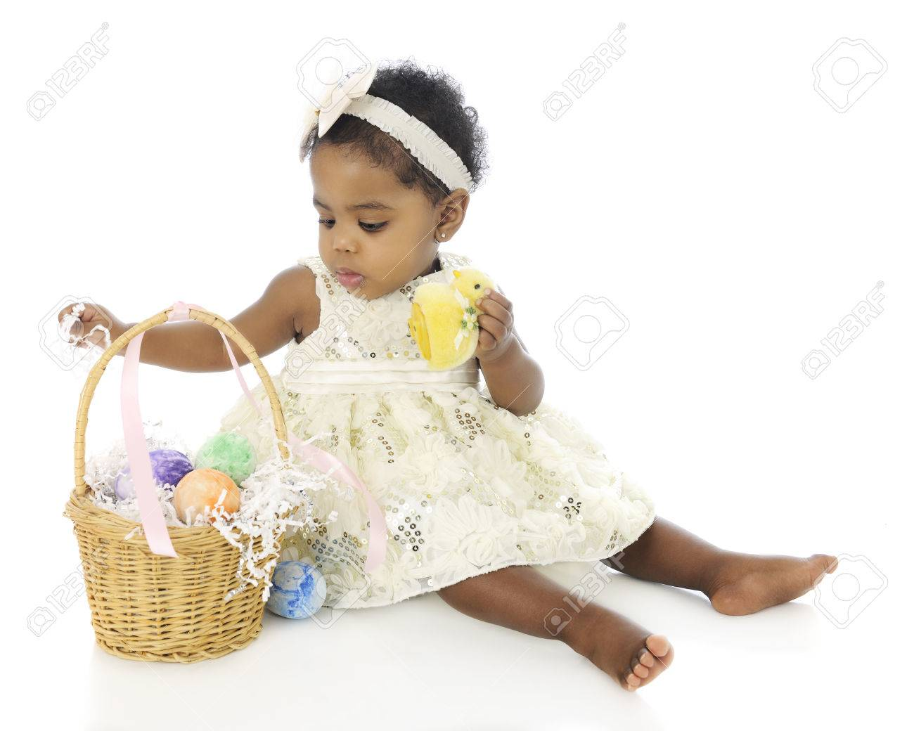 A beautiful baby girl, all dressed up, exploring her first Easter basket.  On a white background. Stock Photo - 27304295