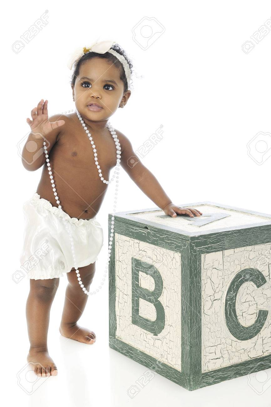 A beautiful baby girl waving as she stands with the help of a giant alphabet block.  On a white background. Stock Photo - 27304292