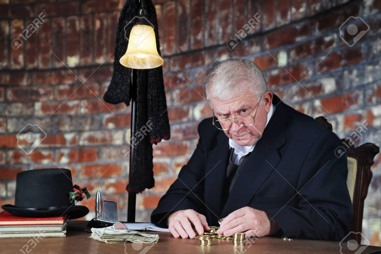 A grumpy old man scowling at the viewer as he counts his gold coins by a stack of large bills. - 32442008
