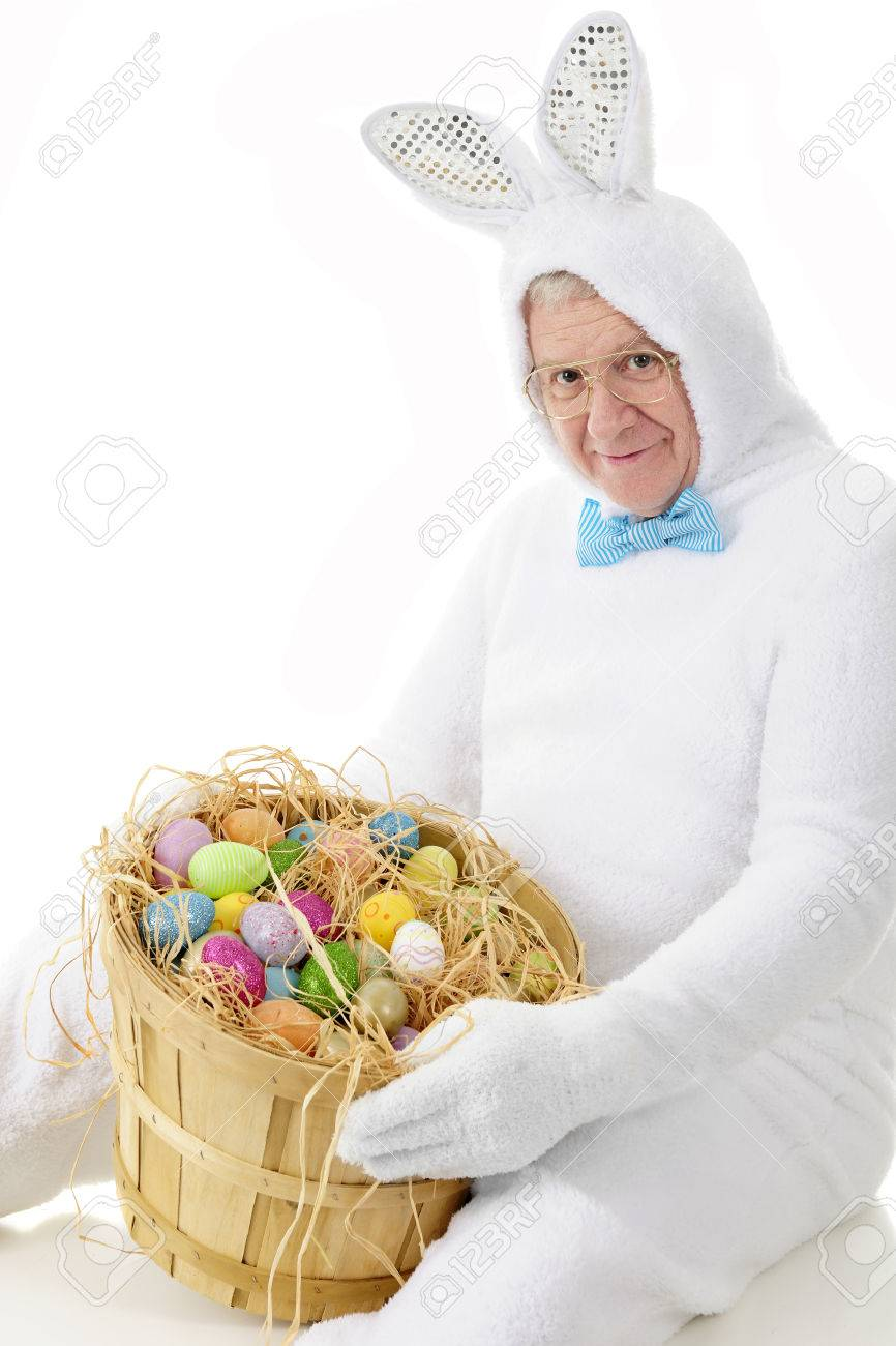 A senior adult man in an easter bunny outfit happily showing a senior adult man in an easter bunny outfit happily showing off a bushel of colorful negle Images