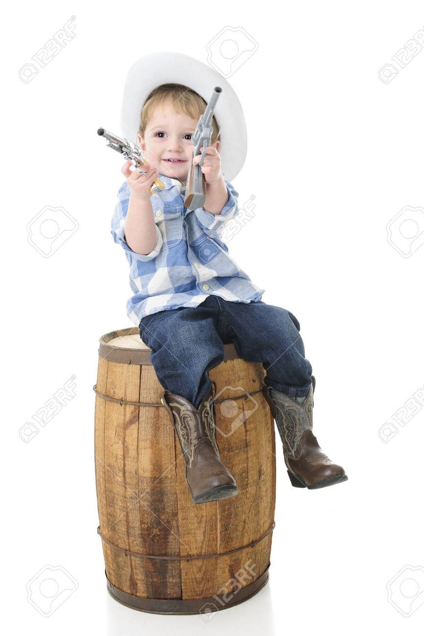 a37478ba5 An adorable 2-year-old cowboy happily sitting on an old barrel..