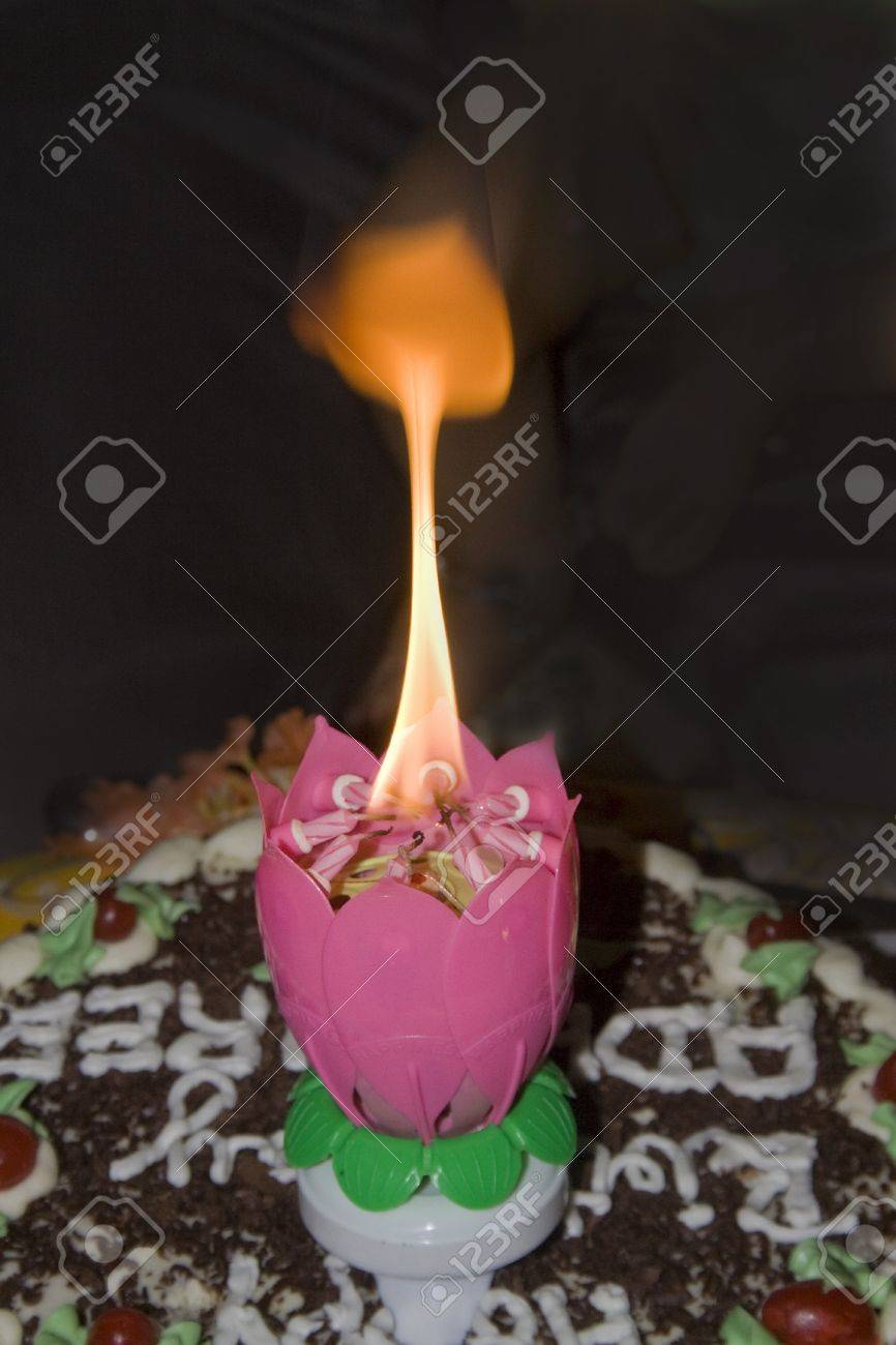 Lighted magic candle in flame which bursts open in the form of lotus Stock Photo - 15142630