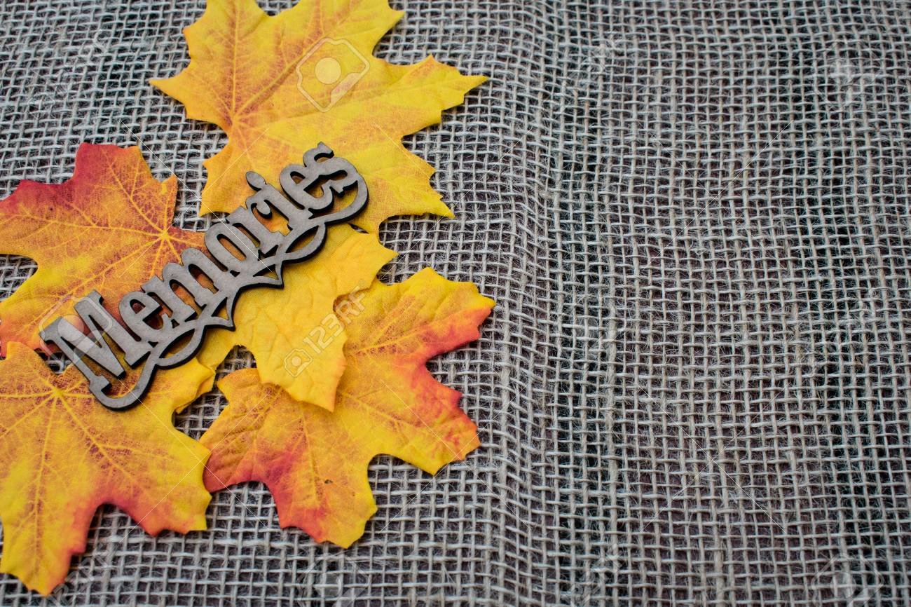 autumn leaves decoration in burlap background with memories tag