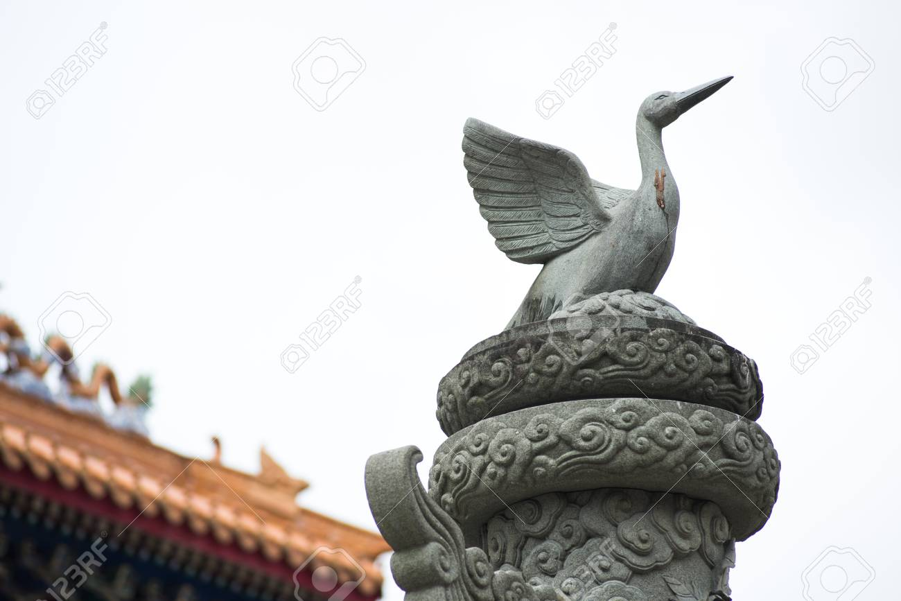 Close up Bird sculpture on top of stone pole in smoke sky - 88203720