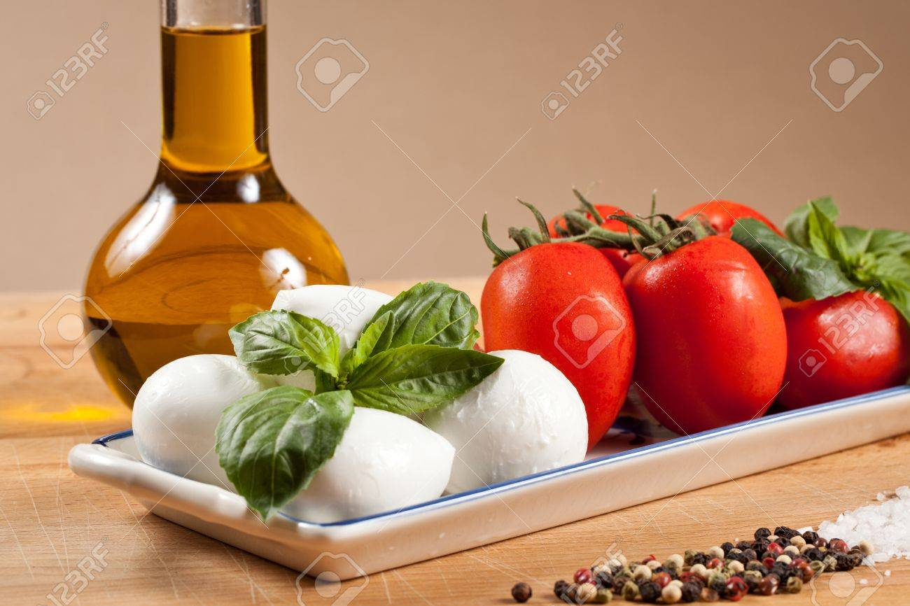 Mozzarella cheese bits and cherry tomatoes with basil leaf. Healty caprese salad with oil bottle, salt and pepper Stock Photo - 11288977