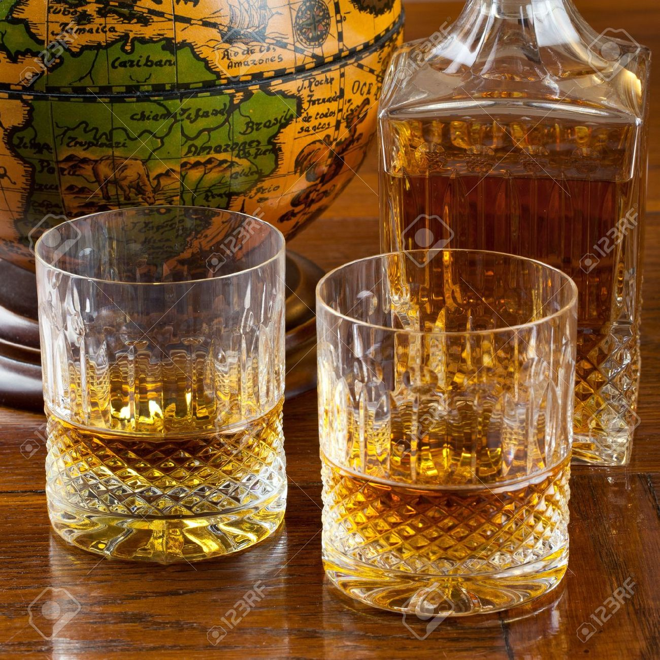Fine bourbon whiskey in crystal bottle and tumbler glasses over a wood antique table with an old globe in background Stock Photo - 11551074