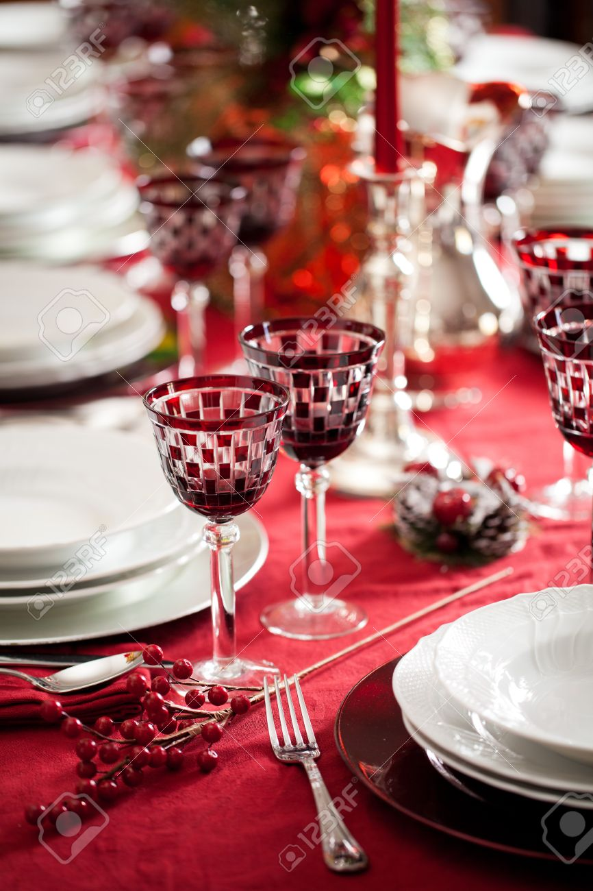 Elegant and decorated table setting with white dishes over a red tablecloth. Silver cutlery and red glasses Stock Photo - 11826830