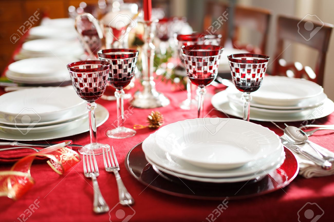 Elegant and decorated table setting with white dishes over a red tablecloth. Silver cutlery and & Elegant And Decorated Table Setting With White Dishes Over A.. Stock ...