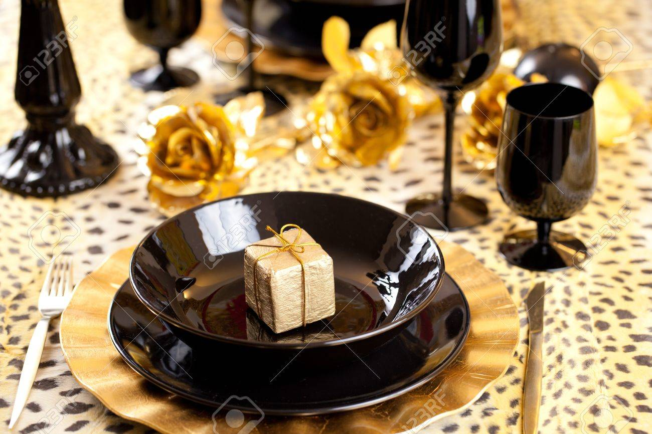 Golden gift box in a black and gold table setting with gold roses over a leopard & Golden Gift Box In A Black And Gold Table Setting With Gold Roses ...