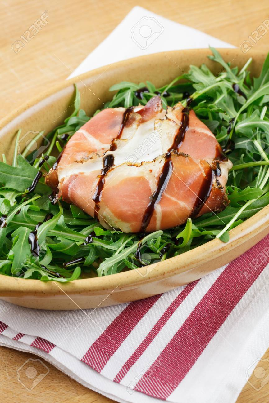 Tomino soft cheese in a bacon wrap, topped with balsamic vinegar, over an rocket bed Stock Photo - 12552057