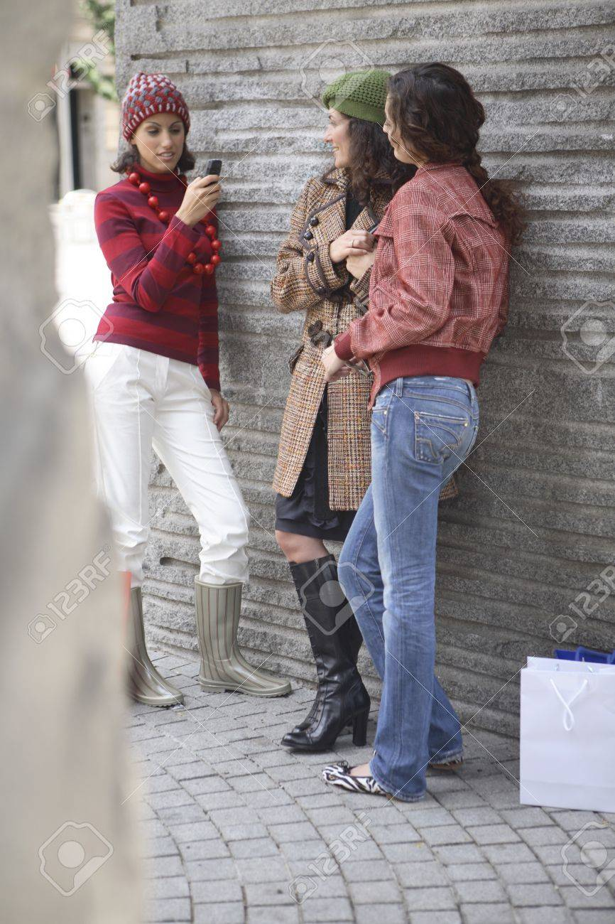 Young latin woman talking on the mobile phone while other two friends chat at her side. Stock Photo - 7475848