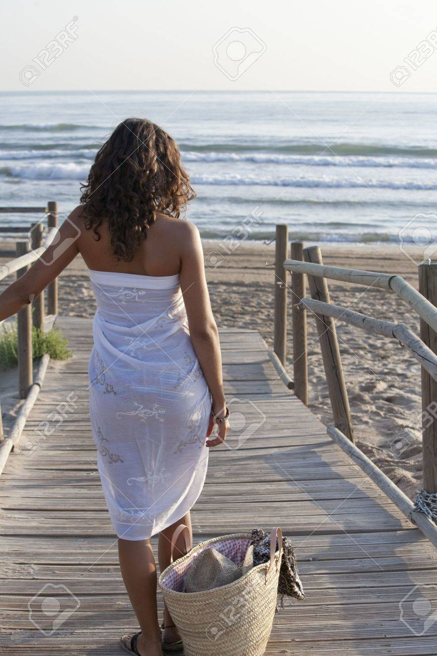Young pretty woman wearing white sarong walking to the beach. Stock Photo - 8088936