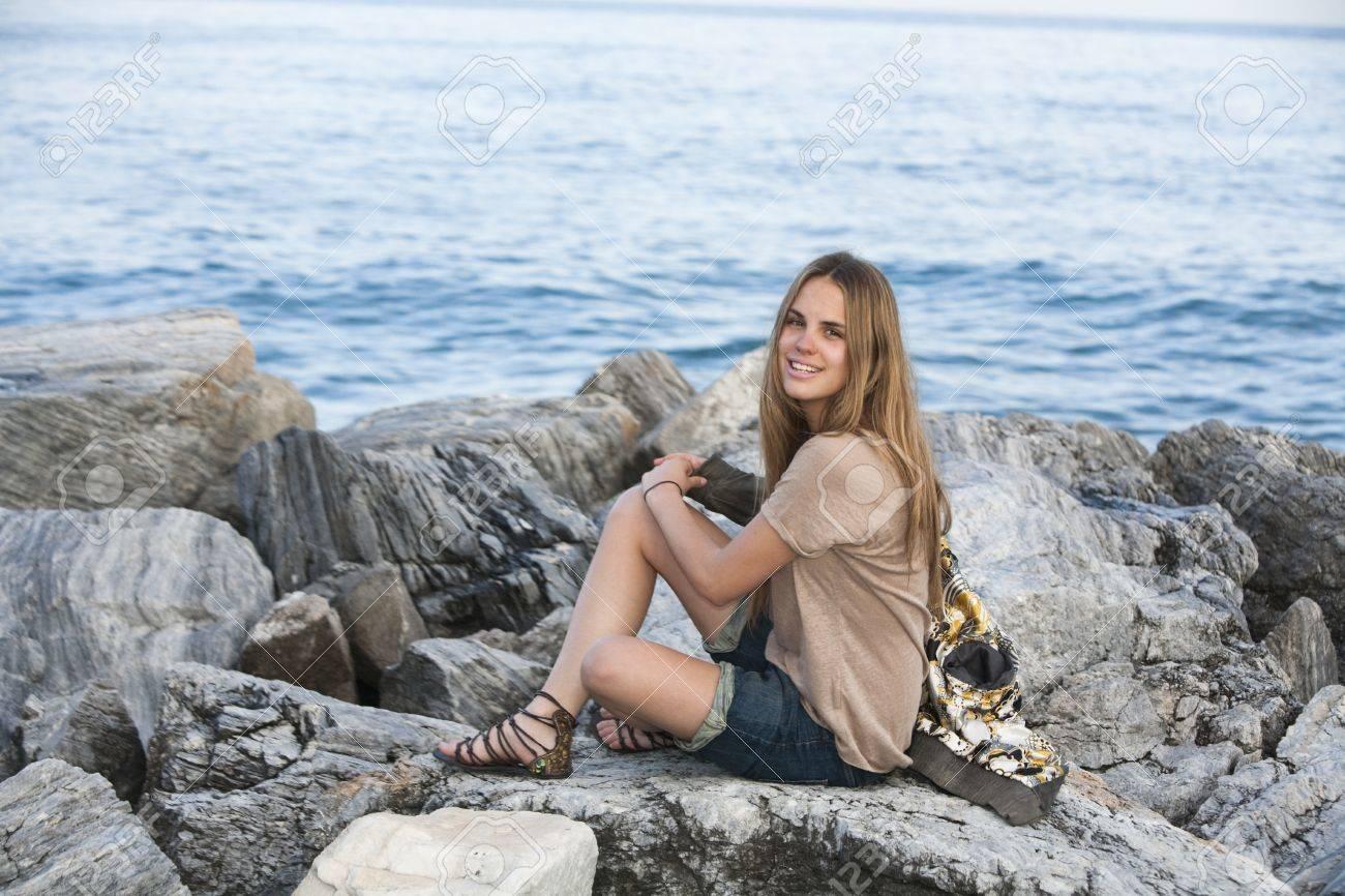 Portrait of young girl on rocks of breakwater at Puerto Banus, Marbella, Spain. Stock Photo - 9467178