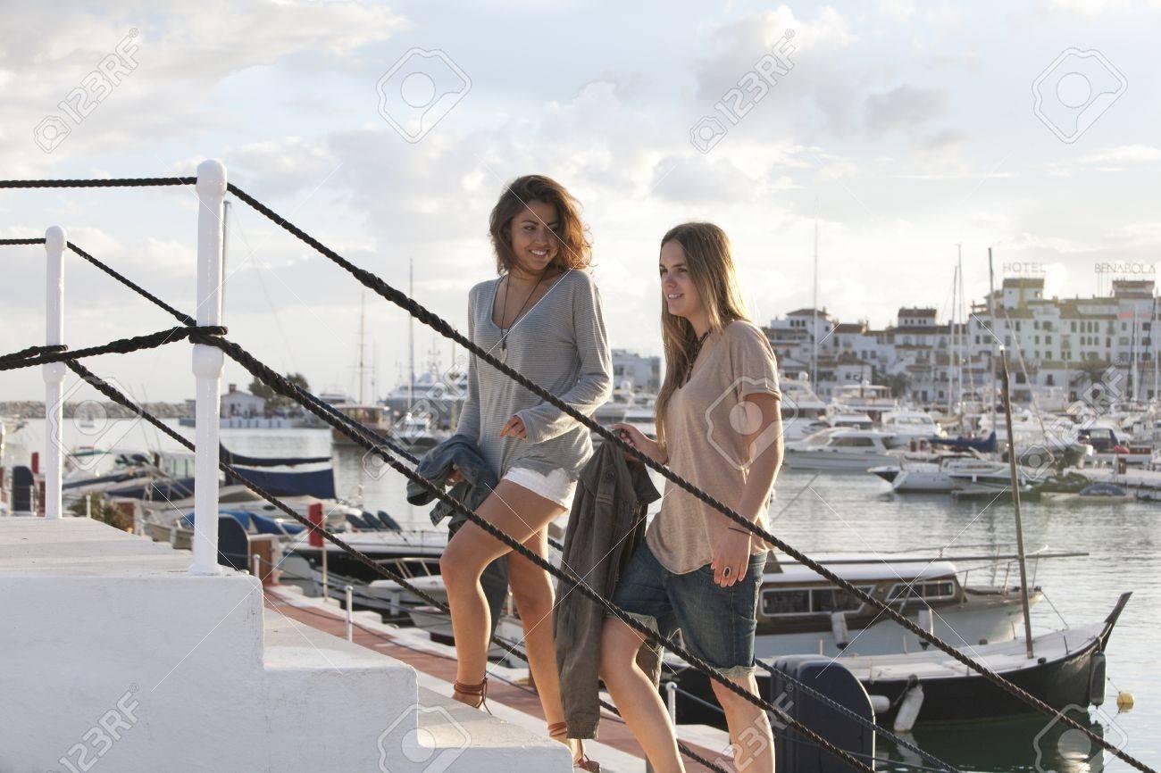 Two young girl friends at the docks of Puerto Banus, Marbella, Malaga, Spain. Stock Photo - 9638605