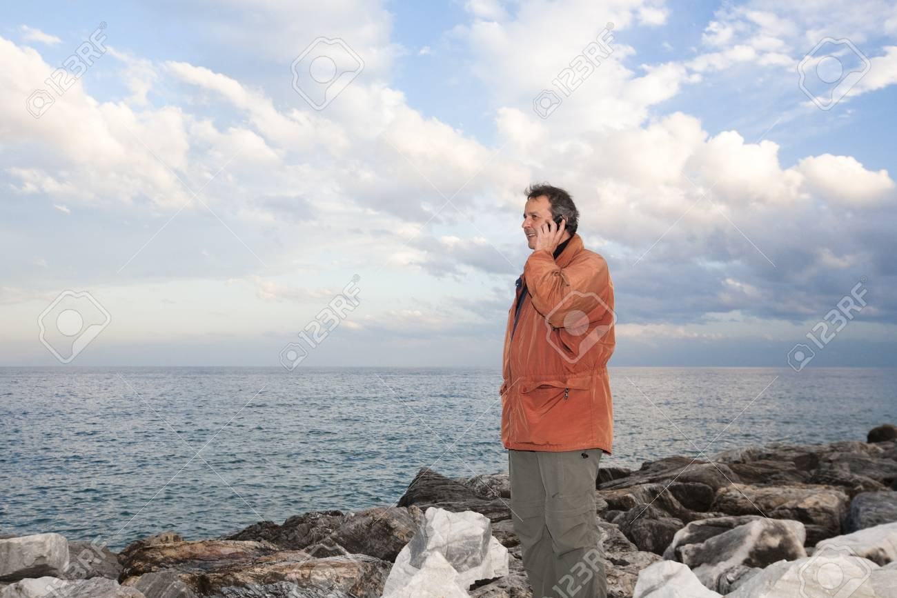 Adult man talking on his mobile phone at harbour of Puerto Banus, Marbella, Spain. Stock Photo - 9638607