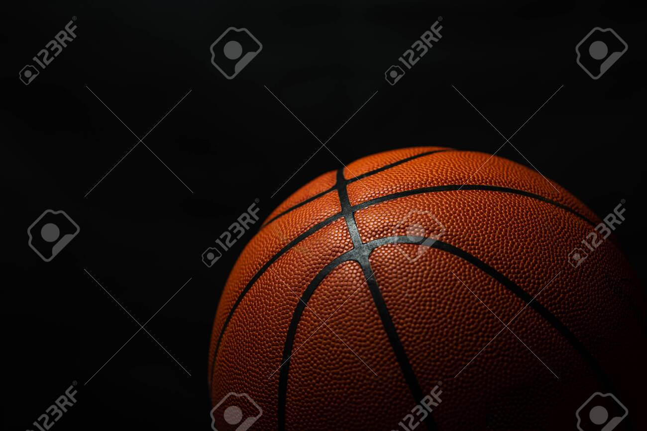 Basketball under the light with a black background - 137845679