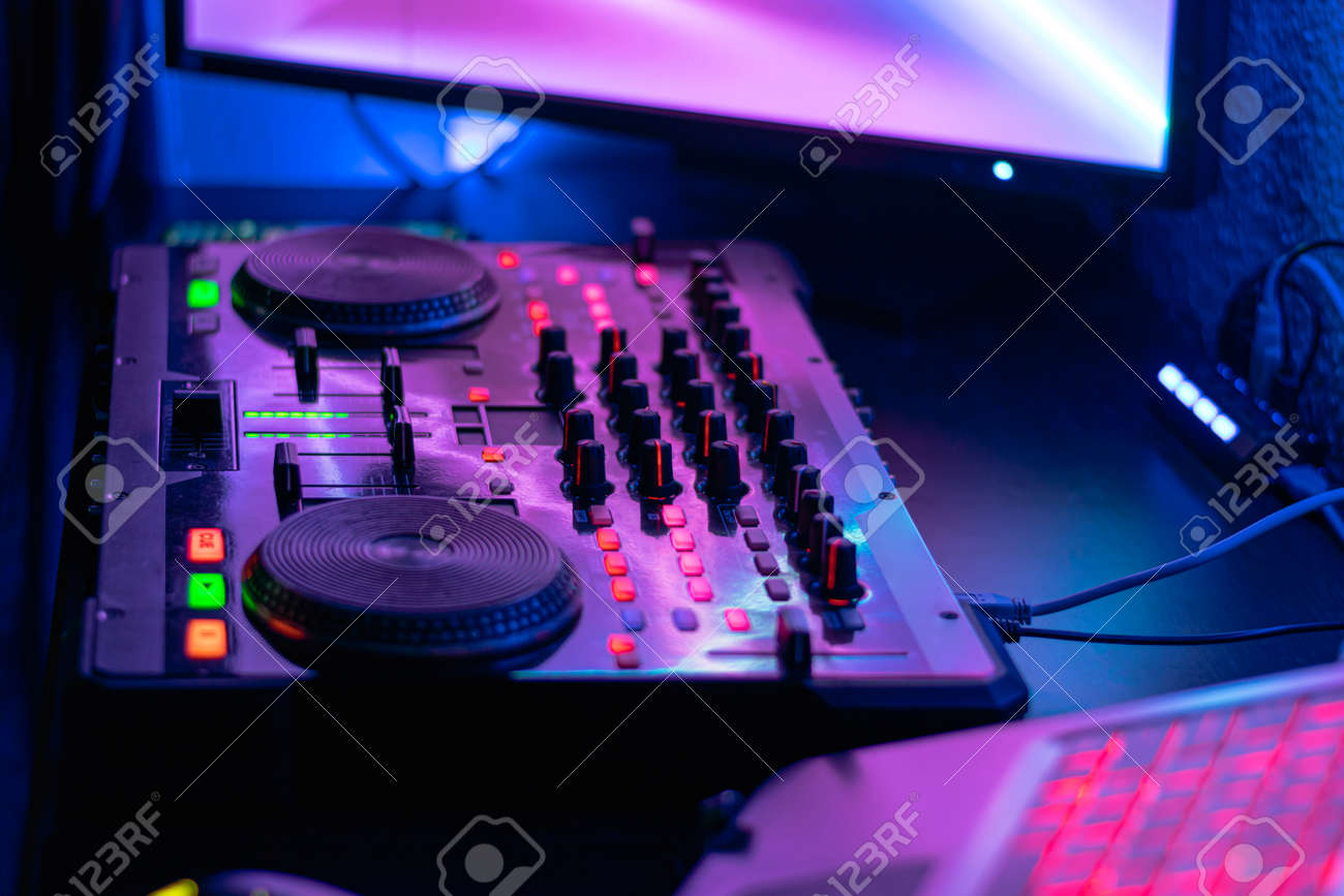 dj table with headphones mixing music flashy colors blue purple - 157944279