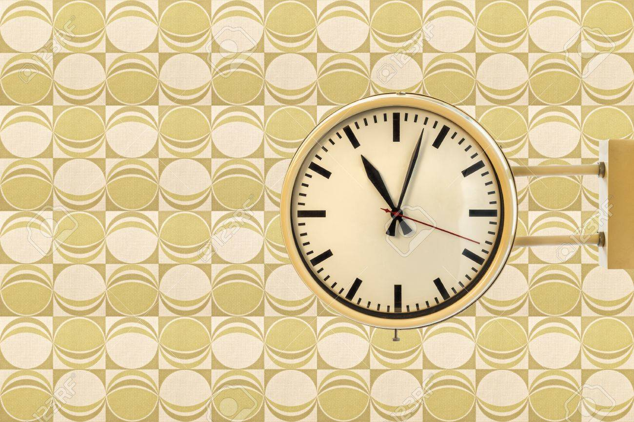 Seventies Vintage Office Clock Against A Retro Wallpaper Background With Green Circles Stock Photo