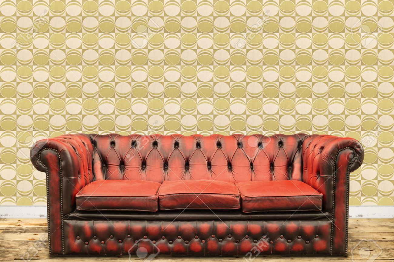 Retro styled image of an old sofa against a vintage wallpaper wall with a green circle print Stock Photo - 18928949