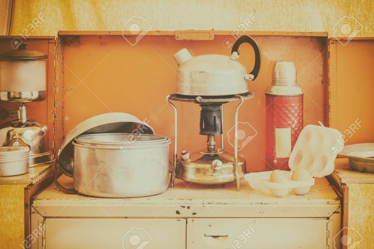 Retro styled image of a vintage caravan kitchen interior with stove and kettle - 121849258