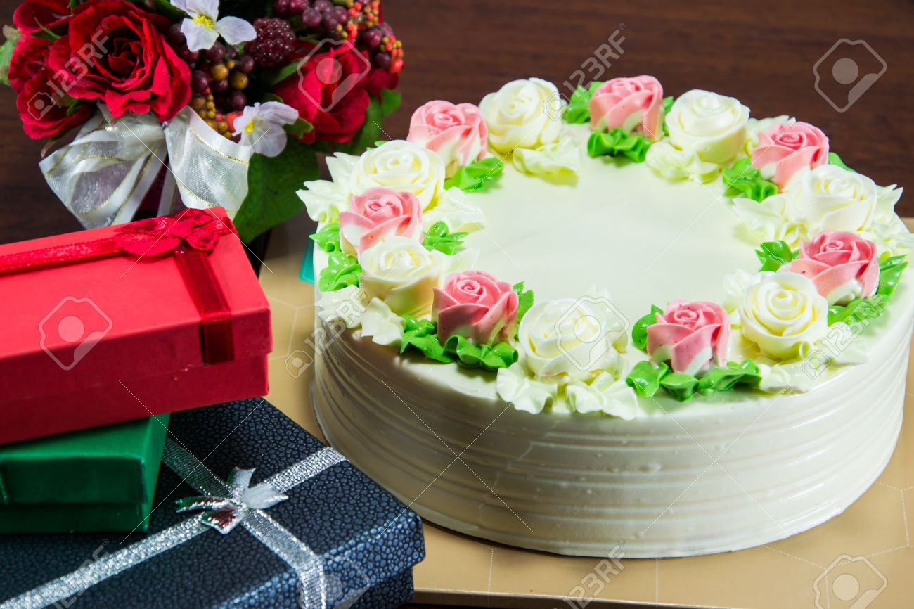 Birthday Cake With Flowers And Gift On Wood Table Stock Photo