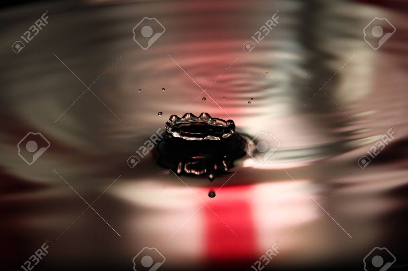 Closeup Pictures Red Background of Water drops a beautiful shape in Basin. Stock Photo - 22174674
