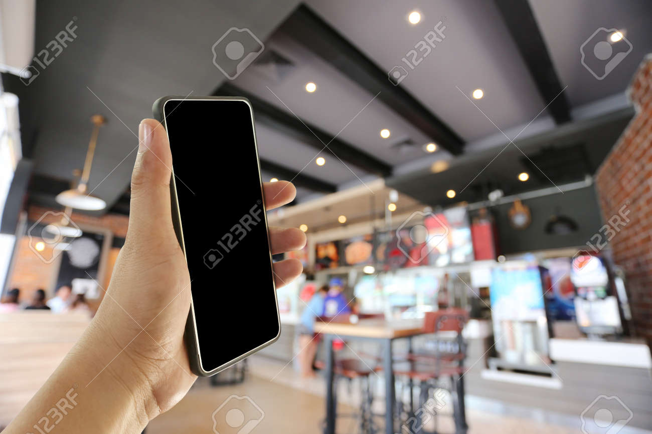 Hand of a man holding smart phone device in the coffee cafe background and have copy space for design. - 135706888