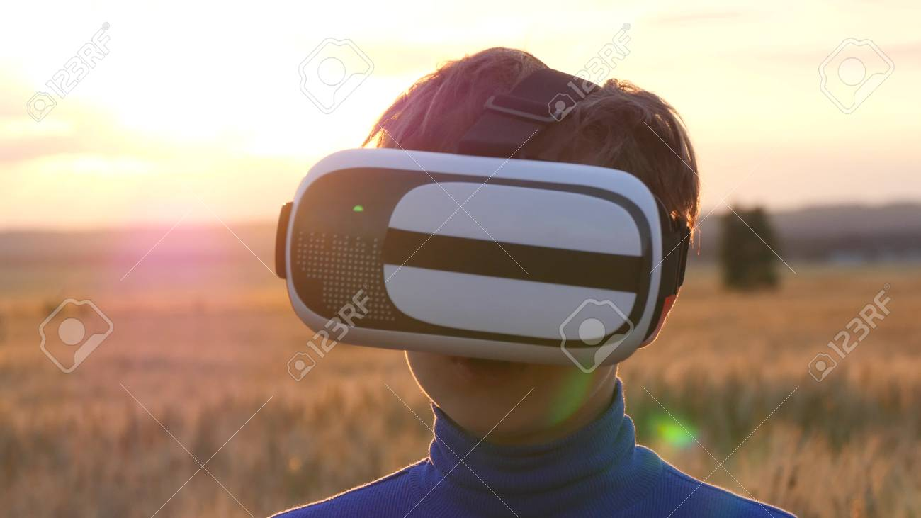 A boy stands in a wheat field at sunset in virtual glasses. Playing outdoors on a sunny day - 88931344