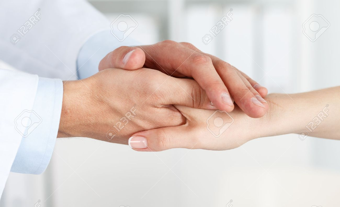Friendly male doctor's hands holding female patient's hand for encouragement and empathy. Partnership, trust and medical ethics concept. Bad news lessening and support. Patient cheering and support - 42889828