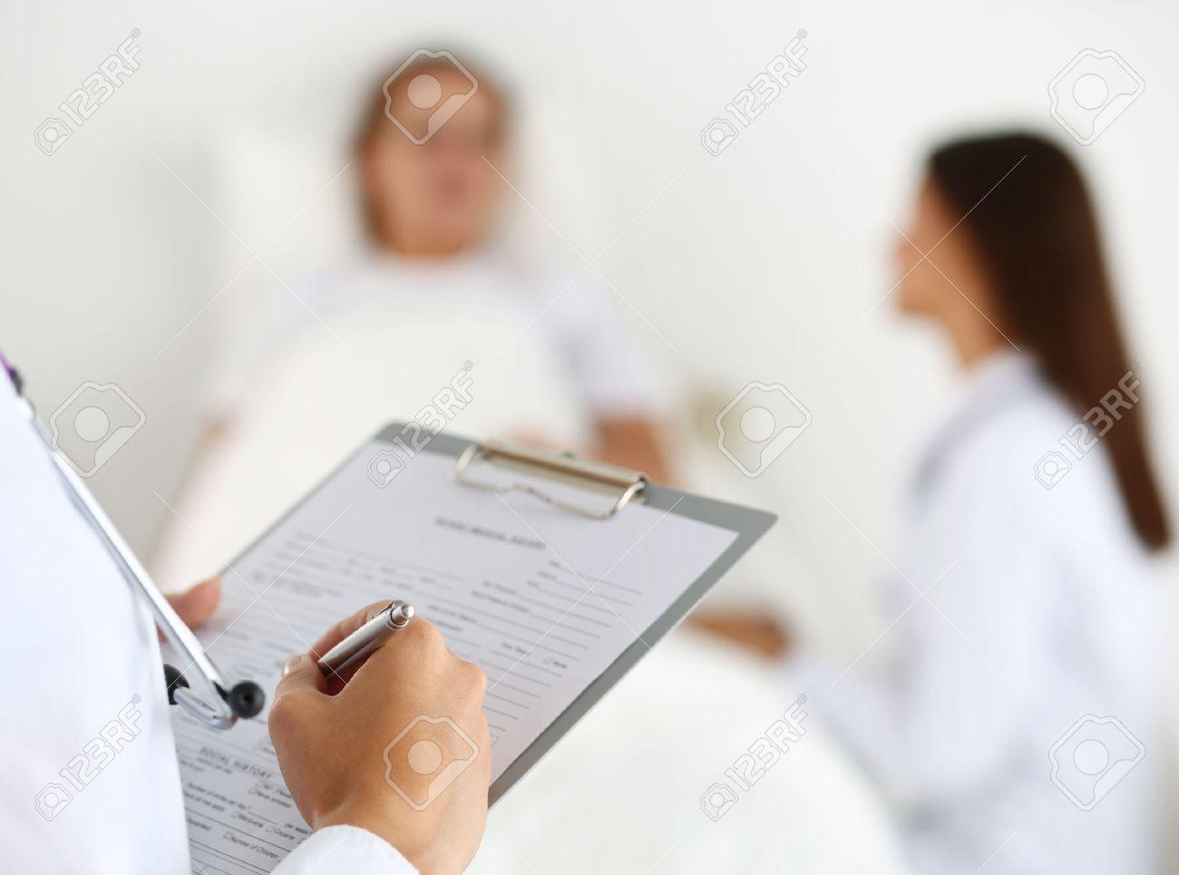 Female Medicine Doctor Filling In Patient Medical History