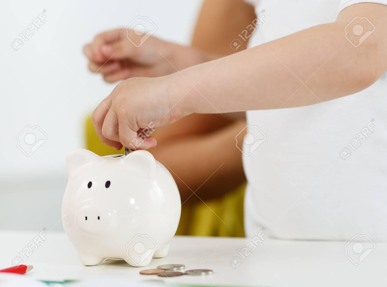 Child Hand Setzen Stift Geld Münzen In Weiß Sparschwein Slot