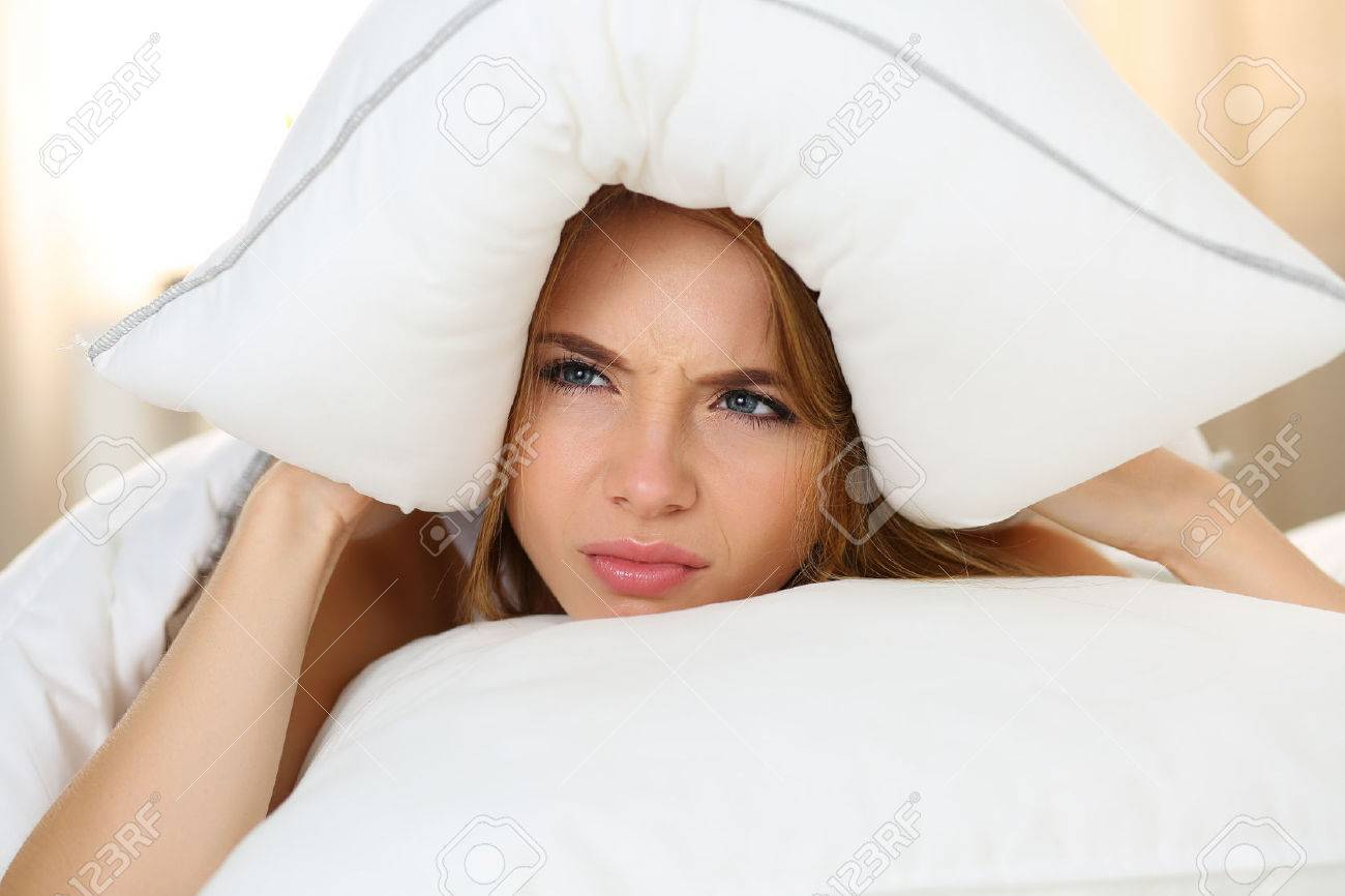 Young beautiful woman lying in bed suffering with insomnia covering head and ears with pillow and making unpleasant face. Noisy neighbour, stress, alarm sound, prevent from sleep concept - 46189010