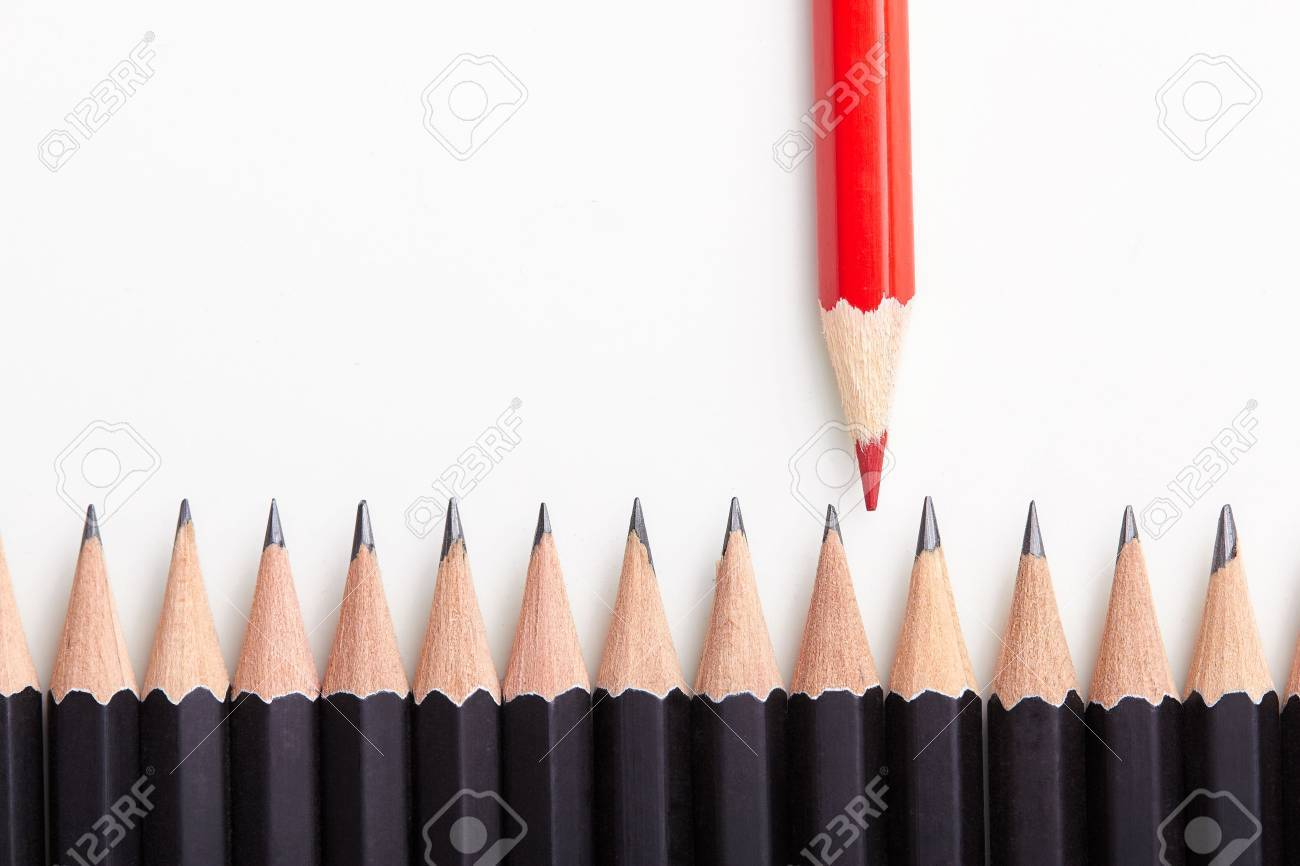 Red pencil standing out from crowd of plenty identical black fellows on white table. - 47107568