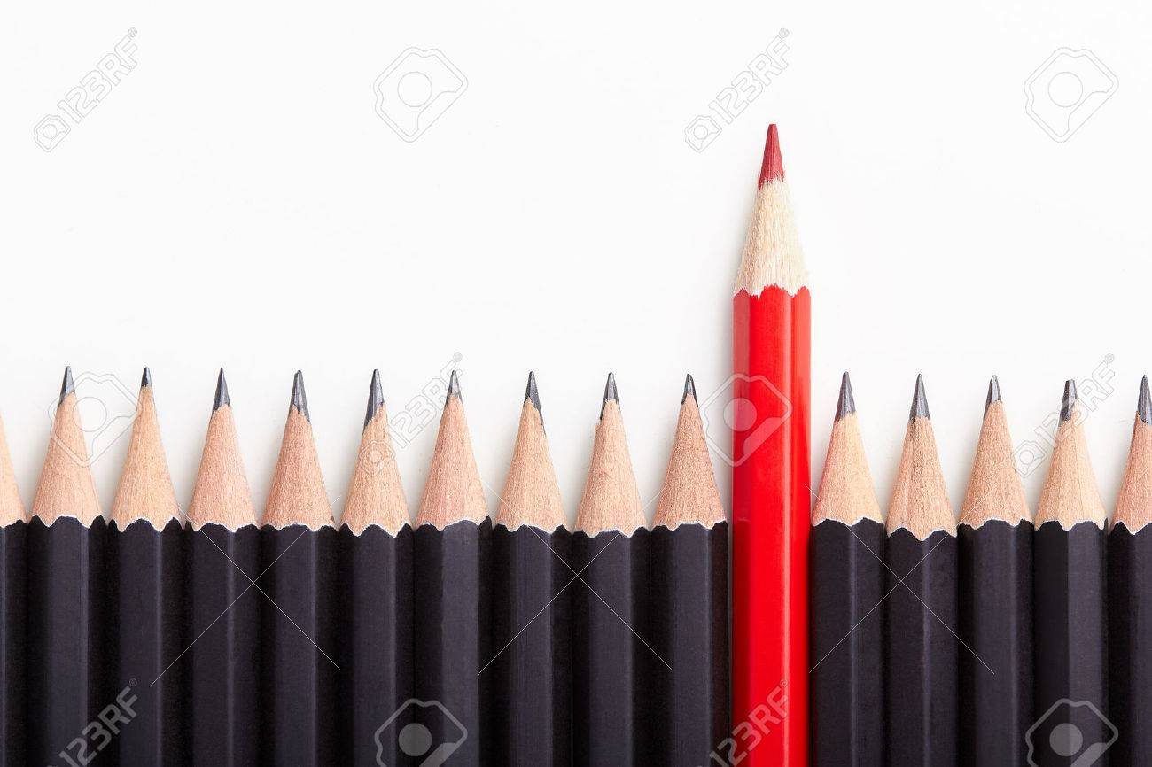 Red pencil standing out from crowd of plenty identical black fellows on white table. Stock Photo - 47107557