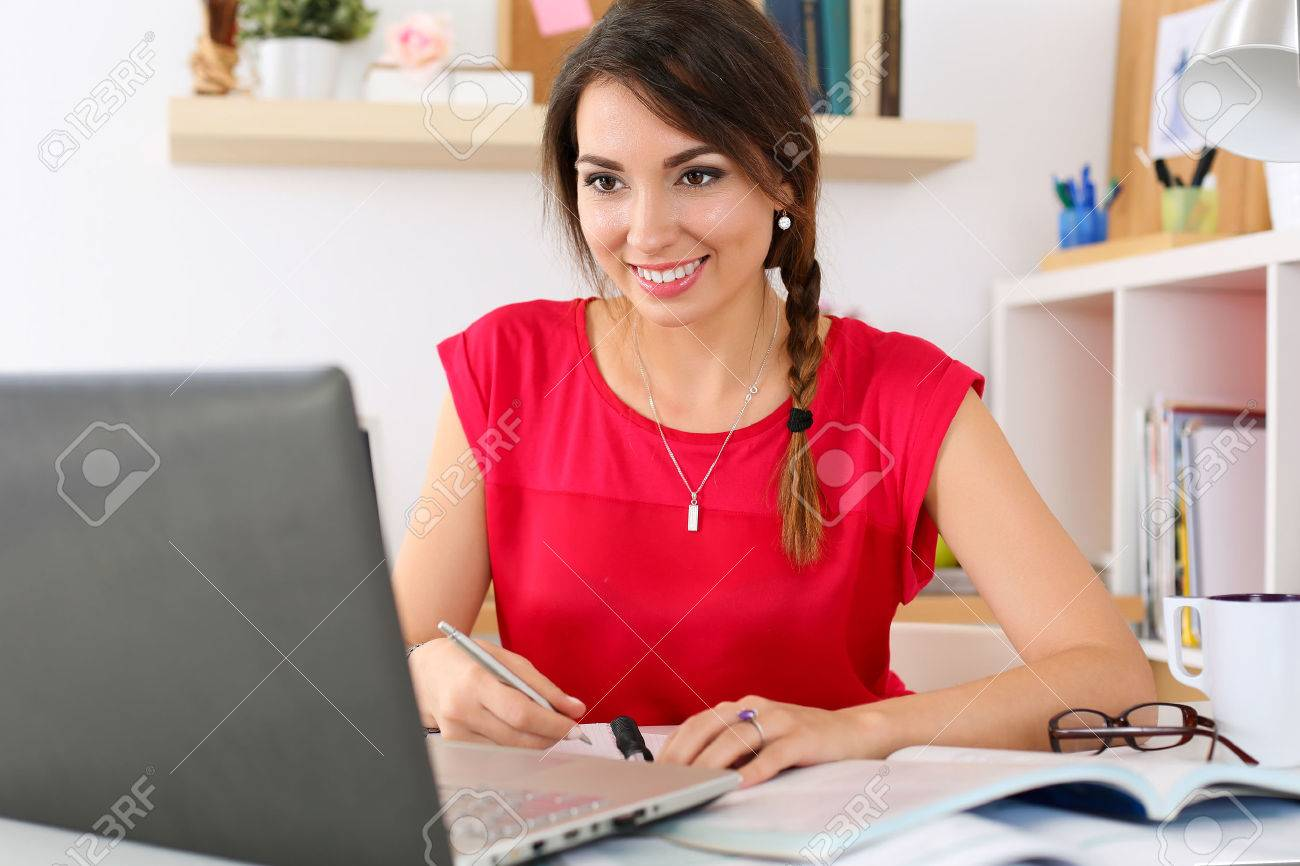 Beautiful smiling female student using online education service. Young woman in library or home room looking in laptop display watching training course. Modern study technology concept - 47986749