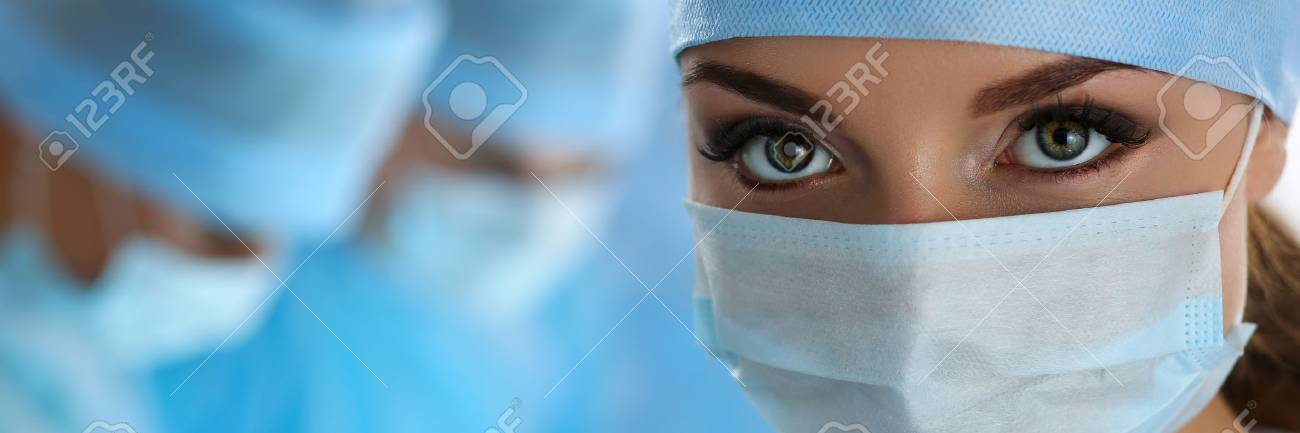 Three surgeons at work operating in surgical theatre. Resuscitation medicine team wearing protective masks saving patient. Surgery and emergency concept. Female surgeon portrait looking in camera - 49269058