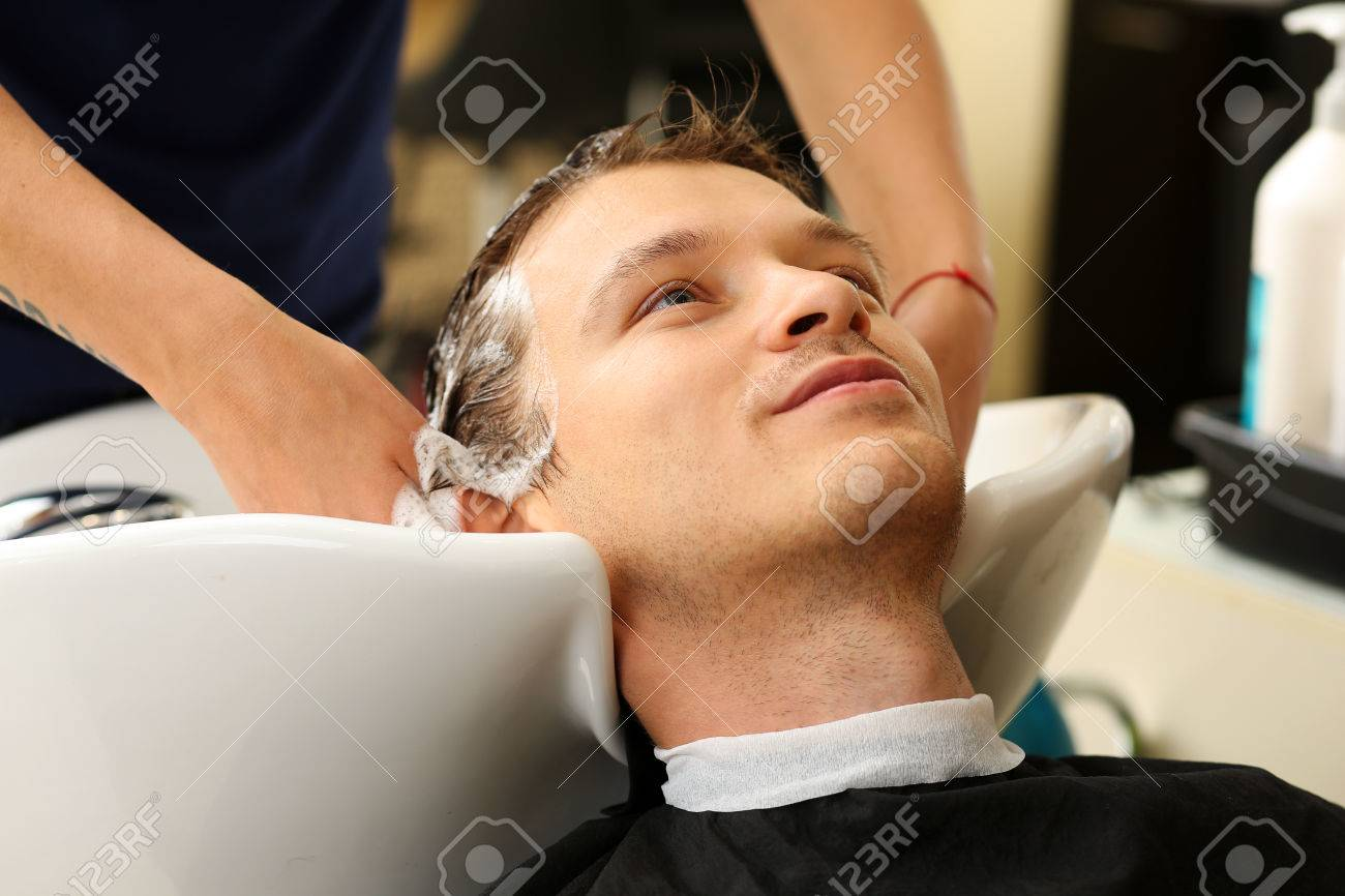 Female Hands Washing Hair To Handsome Smiling Man At Hairdresser