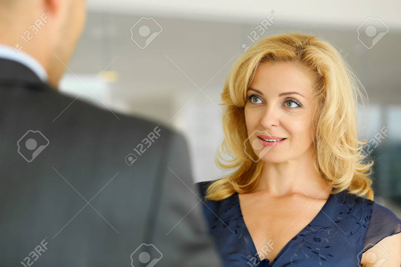 Man and smiling mature woman talking in office. Client or companion support, white collar partner, profit, positive friendly summit, clerk, bargain or deal discussion concept - 70890327