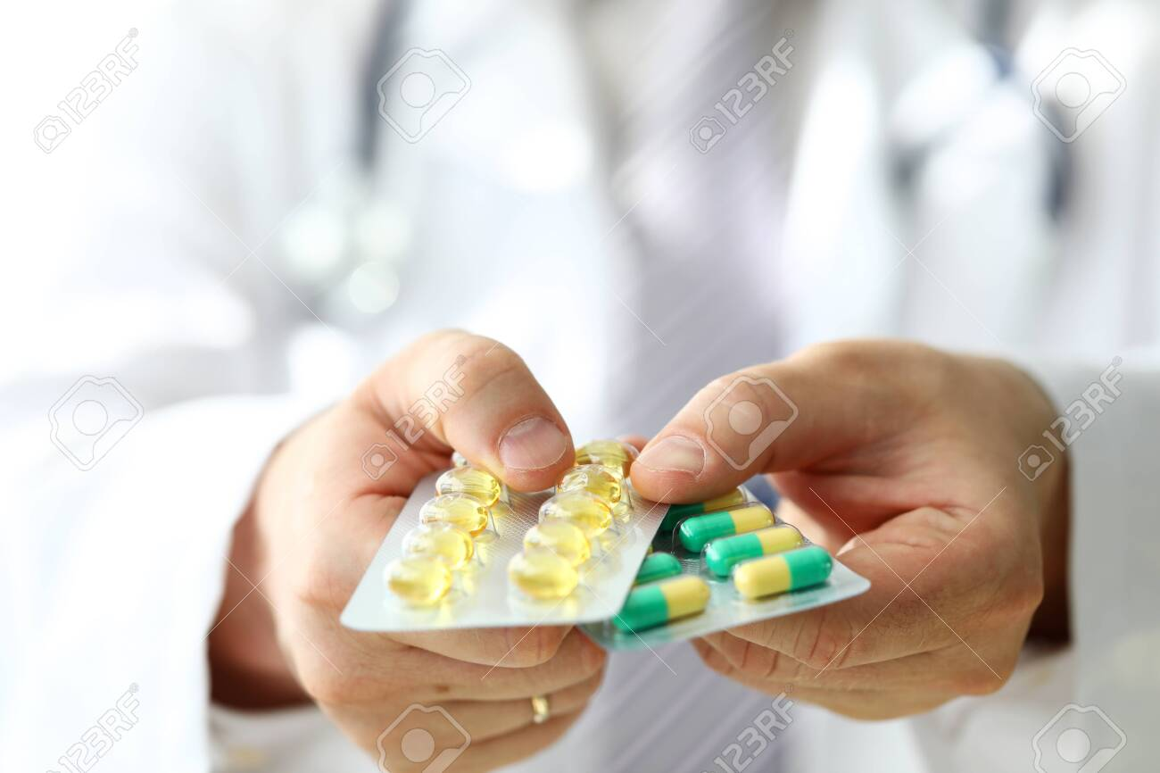 GP in clinic holding pack of different blisters close-up. Life saving medicament prescribing practice and legal drug store concept - 129966144
