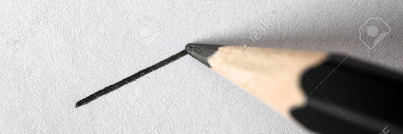 Close-up of black graphite pencil drawing perfectly straight line on textured white sheet. Short direct distance on piece of paper. Art and painting concept - 140935411