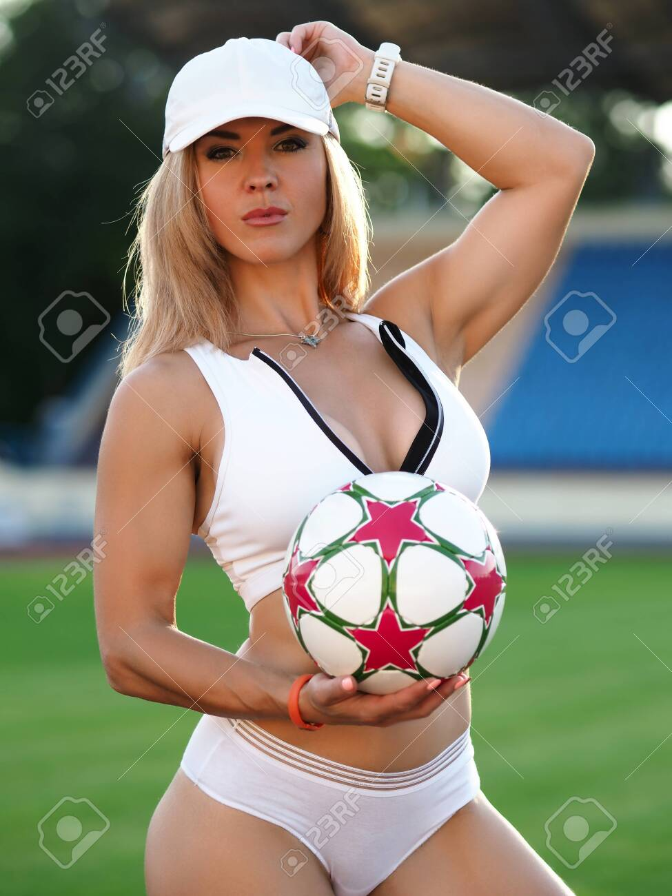 Beautiful girl stands on soccer field with ball. Training or competition for adults. Attractiveness womens football. Photo session at stadium, beautiful photo women for social network - 143773352