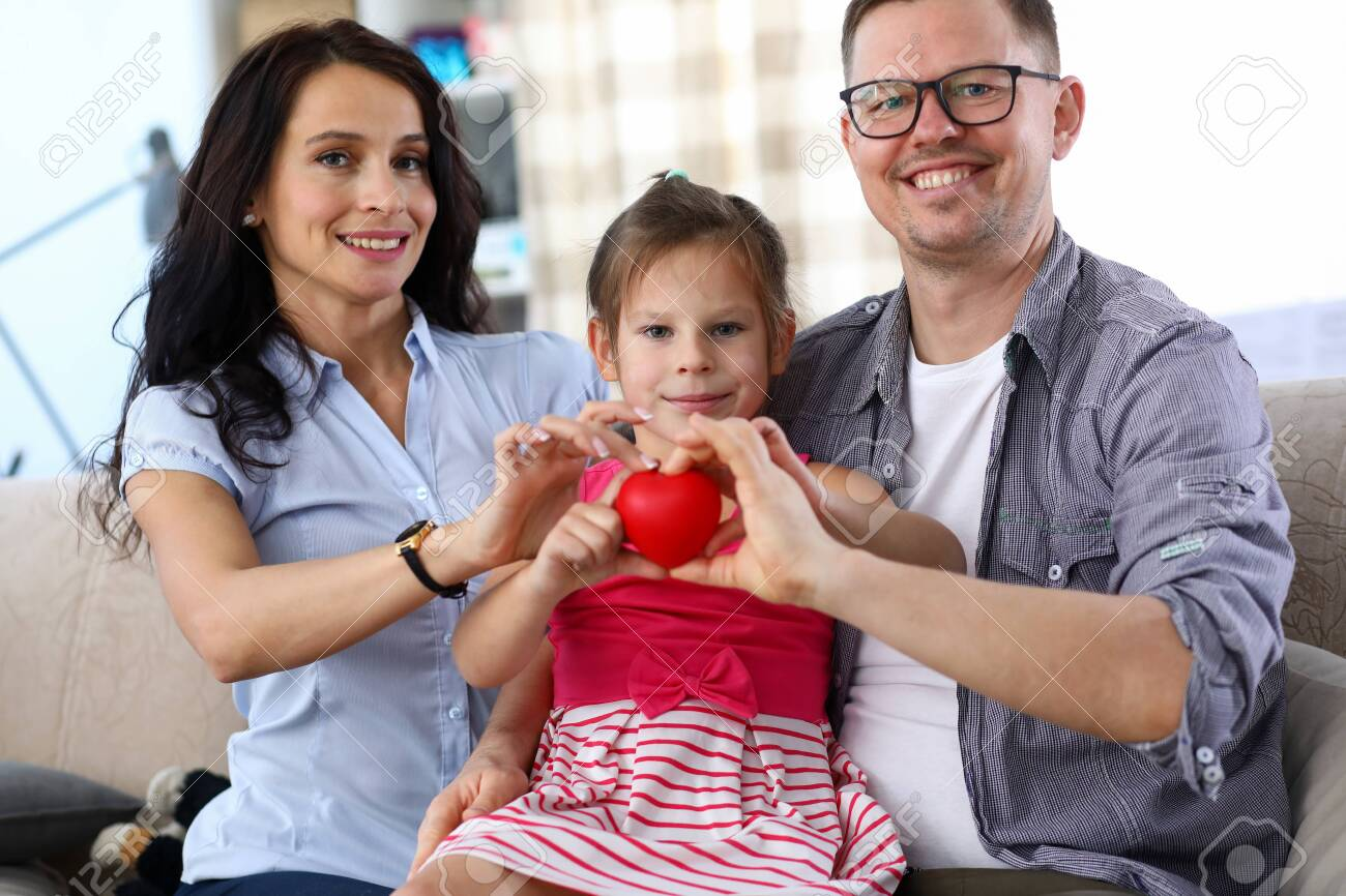 Portrait of cheerful lovely parents and little kid holding red heart together. Cheerful daughter sitting on father knees and smiling sincerely. Happy family concept - 155008549