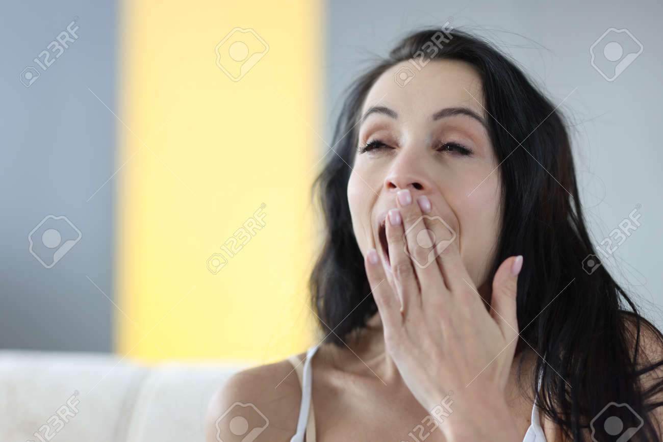 Portrait of young yawning brunette woman at home. Insomnia early awakening concept - 160544092