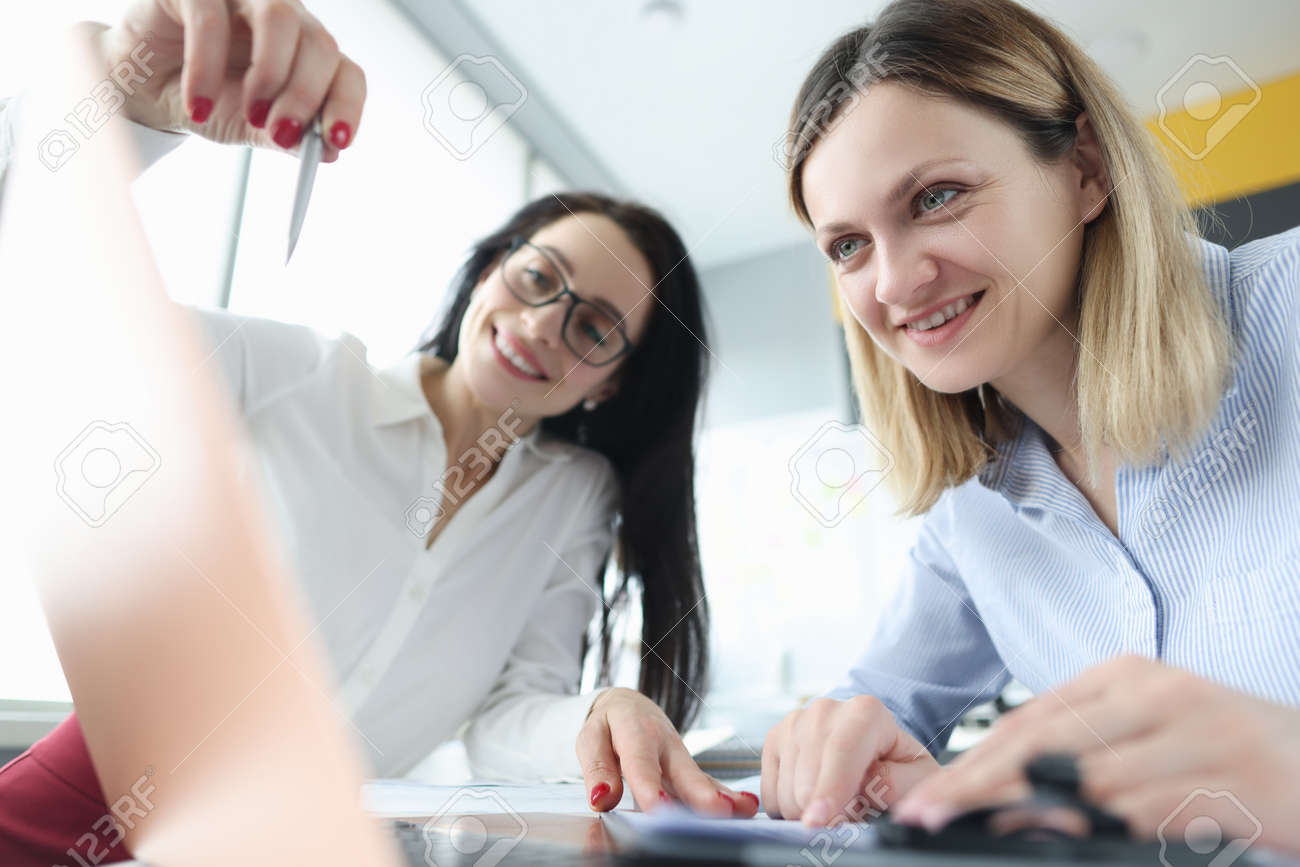 Two businesswoman are discussing business processes by demonstrating them on laptop - 166203470