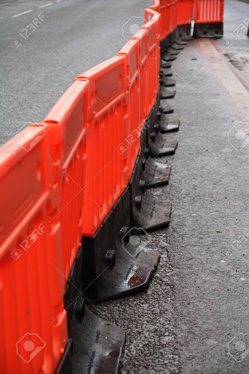 A photo of a temporary walkway with plastic safety barriers on