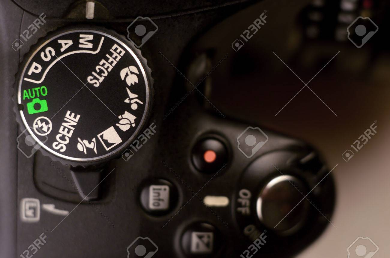 Close-up macro shot of a modern digital SLR camera. Detailed photo of black camera body with buttons to control and switch shooting modes - 71677214