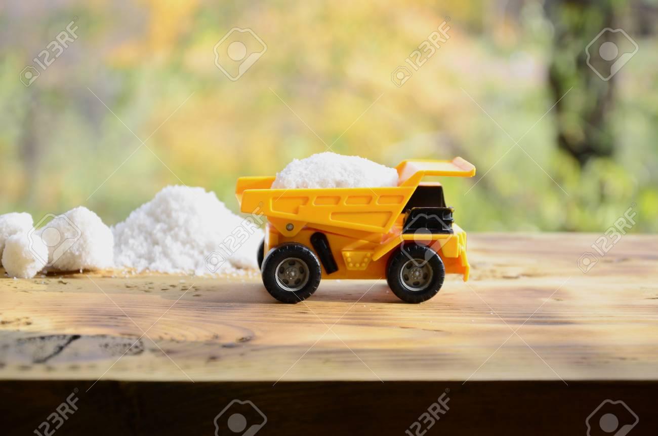 Pila Camión Amarillo SalCoche En De Piedra Cargado Con Una Pequeño Sal Juguete A Superficie Sobre Un Está Blanca Junto Madera 4A35RjL